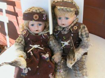 dwie lalki porcelanowe w kartonie na prezent